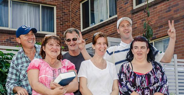 A group of 6 adult tenants smiling and laughing