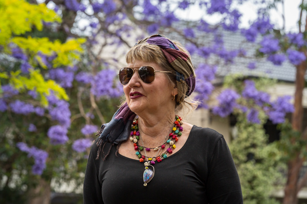 Paddi O'Leary in front of a jacaranda tree.