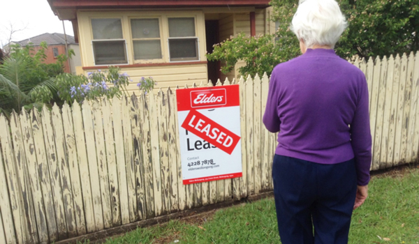 Older woman standing in front of a 'leased' sign