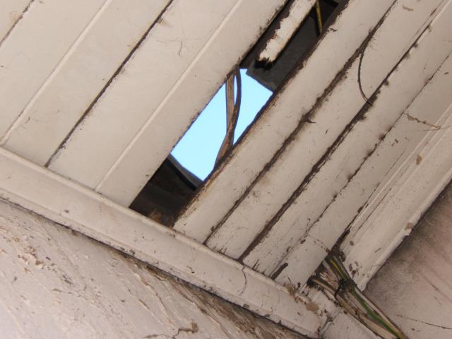 The sky is visible through a roof in disrepair