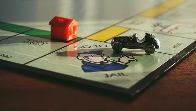 monopoly board game with car playing piece on the 'go to jail' square.