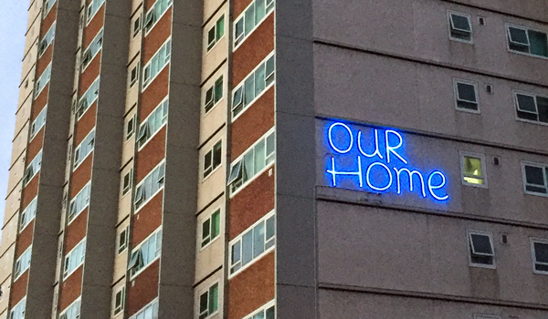 Tall apartment building with 'Our home' on the side
