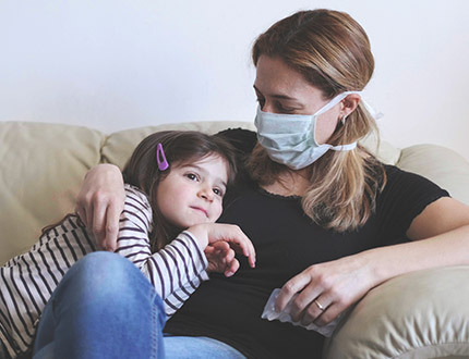 A mother and child sitting on a couch. The mother is wearing a face mask.