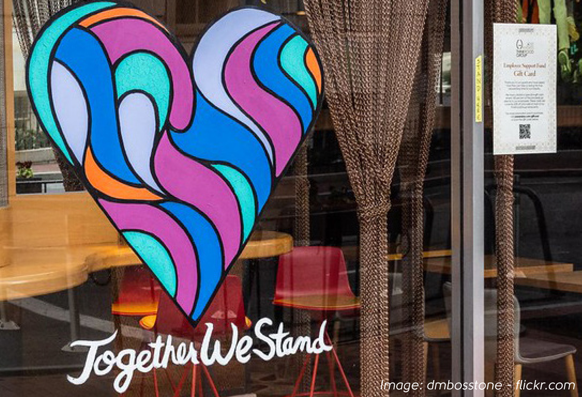 Colourful heart motif on cafe window with text Together We Stand underneath