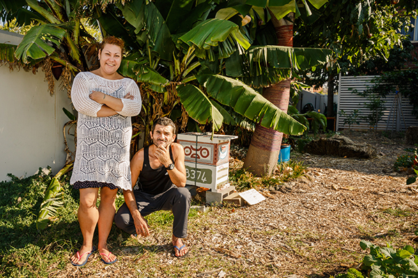 Liezel and Johnny standing next to the beehive