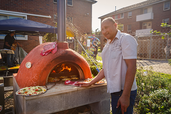 A tenant cooking pizza in the pizza oven